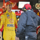Sprint Cup driver Joey Logano, left, celebrates winning the pole for Sunday's NASCAR Sprint Cup race at the Martinsville Speedway in Martinsville, Va., Friday, March 27, 2015. Rain delayed the practice and qualifying for Sunday's STP 500 Sprint Cup race. (AP Photo/Steve Helber)