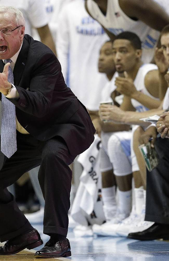 North Carolina coach Roy Williams, left, reacts following a play against Kentucky during the second half of an NCAA college basketball game in Chapel Hill, N.C., Saturday, Dec. 14, 2013. North Carolina won 82-77