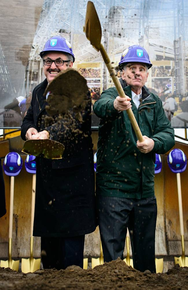 Vikings owner Zygi Wilf, left, throws dirt next to Minnesota Gov. Mark Dayton during the ceremonial groundbreaking for the new Vikings stadium on Tuesday, Dec. 3, 2013, in Minneapolis. After more than a decade of planning, dealing and pleading, the $1 billion project began Tuesday with a formal groundbreaking