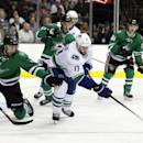Dallas Stars' Brenden Dillon (4) watches as Vancouver Canucks center Ryan Kesler (17) gains control of the puck on an offensive possession in the second period of an NHL hockey game, Thursday, Dec. 19, 2013, in Dallas. (AP Photo/Tony Gutierrez)