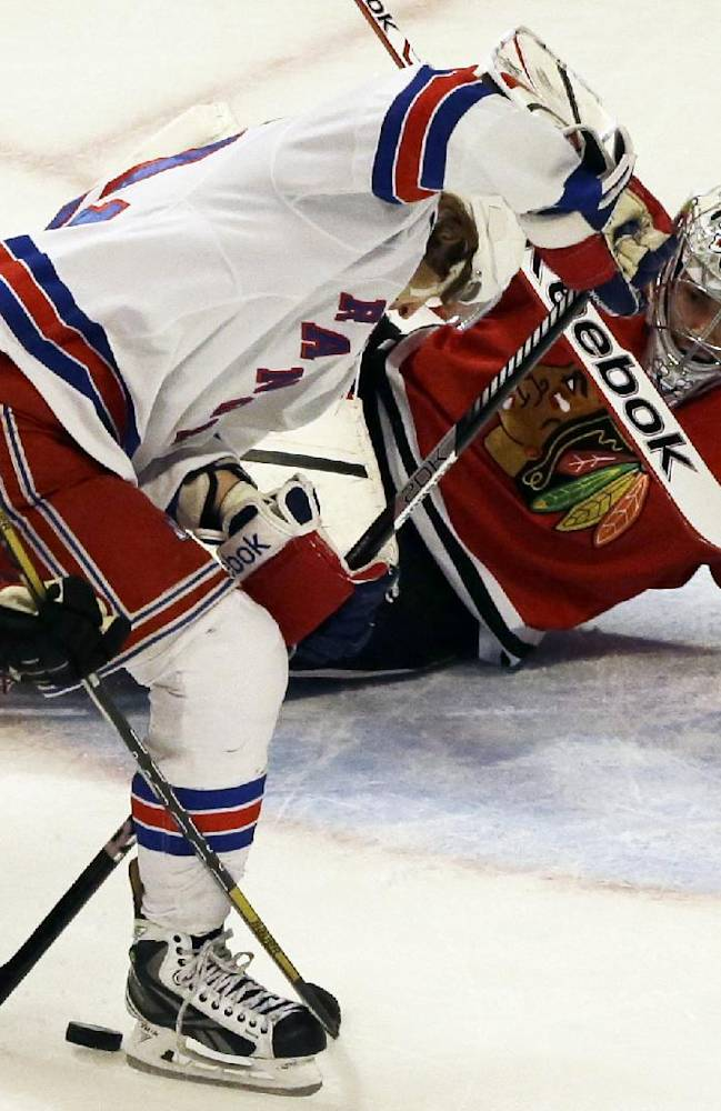 New York Rangers' Carl Hagelin (62), center, scores against Chicago Blackhawks goalie Corey Crawford, right, during the third period of an NHL hockey game in Chicago, Wednesday, Jan. 8, 2014. The Rangers won 3-2