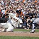 San Francisco Giants' Matt Duffy, left, slides into home plate and scores the Giants' first run as Milwaukee Brewers catcher Jonathan Lucroy, right, waits for the throw in the seventh inning of a baseball game Wednesday, July 29, 2015, in San Francisco. Duffy scored after Hunter Pence doubled to left field. (AP Photo/Eric Risberg)
