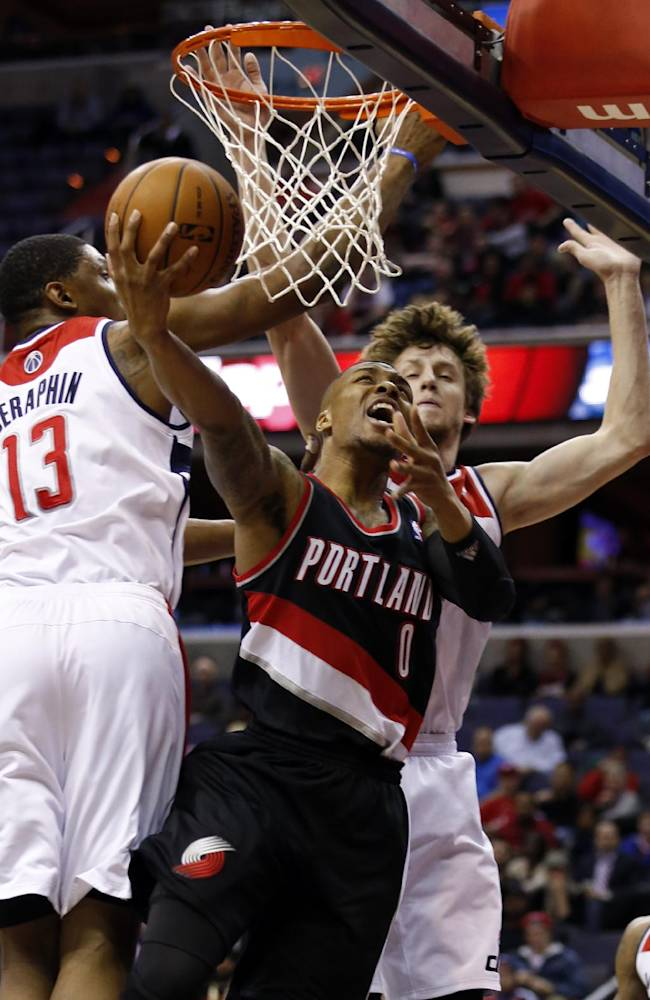 Portland Trail Blazers guard Damian Lillard (0) shoots as he is defended by Washington Wizards center Kevin Seraphin (13), of France, and forward Jan Vesely (24) in the first half of an NBA basketball game, Monday, Feb. 3, 2014, in Washington