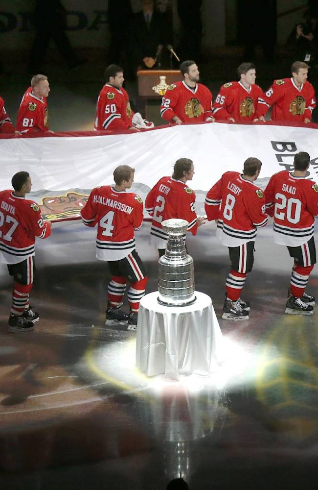 The Chicago Blackhawks carry out the Stanley Cup Championship banner past the Stanley Cup during a ceremony before an NHL hockey game between the Blackhawks and the Washington Capitals, Tuesday, Oct. 1, 2013, in Chicago