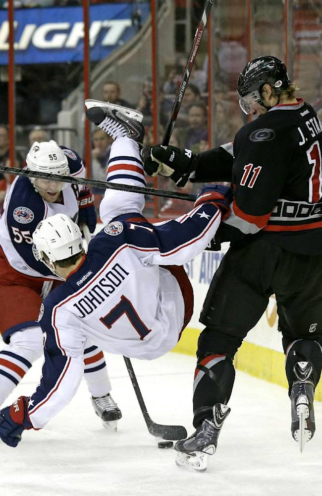Columbus Blue Jackets' Jack Johnson (7) falls as Carolina Hurricanes ' Jordan Staal (11) and Blue Jackets' Mark Letestu (55) chase the puck during the second period of an NHL hockey game in Raleigh, N.C., Monday, Jan. 27, 2014
