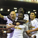 Swansea's Marvin Emnes, foreground centre, celebrates with teammates after scoring against Liverpool during the English League Cup soccer match between Liverpool and Swansea at Anfield Stadium, Liverpool, England, Tuesday Oct. 28, 2014