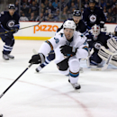 San Jose Sharks' Logan Couture (39) reaches for the puck in front of Winnipeg Jets goaltender Michael Hutchinson (34) during the first period of an NHL hockey game Monday, Jan. 5, 2015, in Winnipeg, Manitoba The Associated Press
