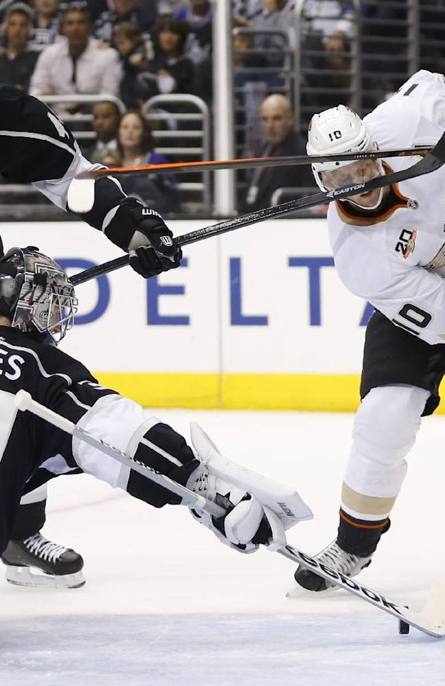 Anaheim Ducks right wing Corey Perry, right, takes a high stick to the face from Los Angeles Kings defenseman Robyn Regehr, left, as Los Angeles Kings goalie Martin Jones makes a save during the first period of an NHL hockey game in Los Angeles, Saturday, March 15, 2014