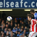 Chelsea's Gary Cahill, right, jumps and leans into Stoke City's Peter Crouch as they vie to head the ball during their English Premier League soccer match between Chelsea and Stoke City at Stamford Bridge stadium in London, Saturday, April, 5, 2014