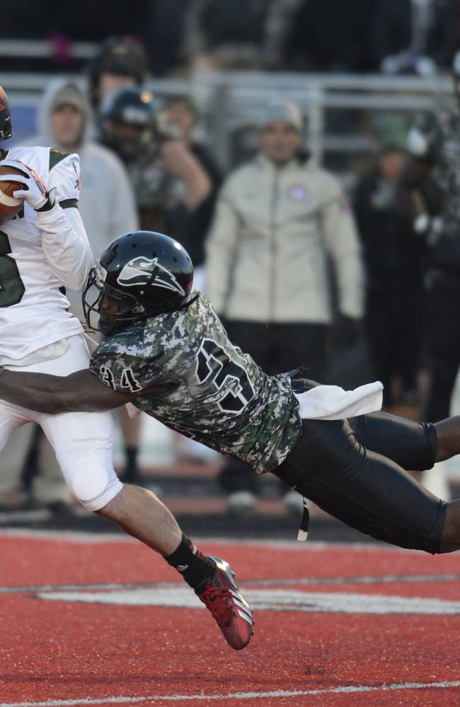 Eastern Washington's wide receiver Cory Mitchell (6) makes a first down reception as Portland State's Mishawn Cummings (34) flies in for the tackle during the first half of a college football game on Saturday, Nov. 23, 2013, in Cheney, Wash