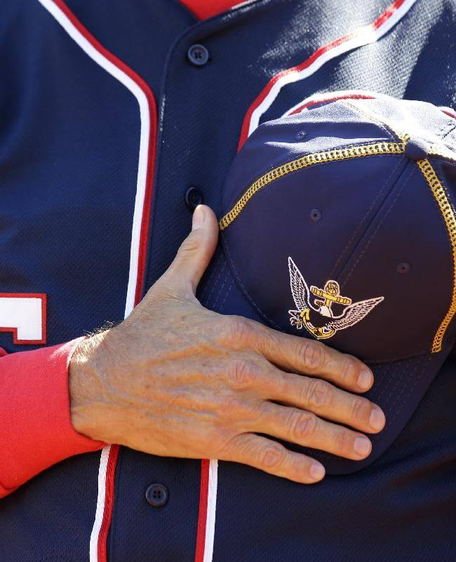 Washington Nationals manager Davey Johnson holds a Navy hat over his heart during a moment of silence before a baseball game against the Atlanta Braves at Nationals Park Tuesday, Sept. 17, 2013, in Washington. The Nationals wore Navy hats, presented to them before the game, by Adm. James A. Winnefield, vice-chairman of the Joint Chiefs of Staff,  to honor those killed and injured in the attack Monday at the nearby Washington Navy Yard