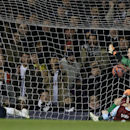 Tottenham's Danny Rose, left, scores his sides fourth goal past Burnley's goalkeeper Tom Heaton during the English FA Cup third round replay soccer match between Tottenham Hotspur and Burnley at the White Hart Lane stadium in London, Wednesday, Jan. 14, 2