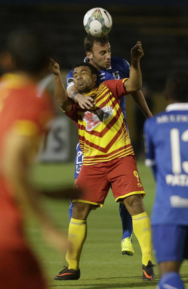 Mariano Uglessich of Ecuador's Universidad Catolica , center back, fights for the ball with Edwin Aguilar of Venezuela's Deportivo Anzoategui during a Copa Sudamericana soccer match in Quito, Ecuador, Tuesday, Aug. 19, 2014