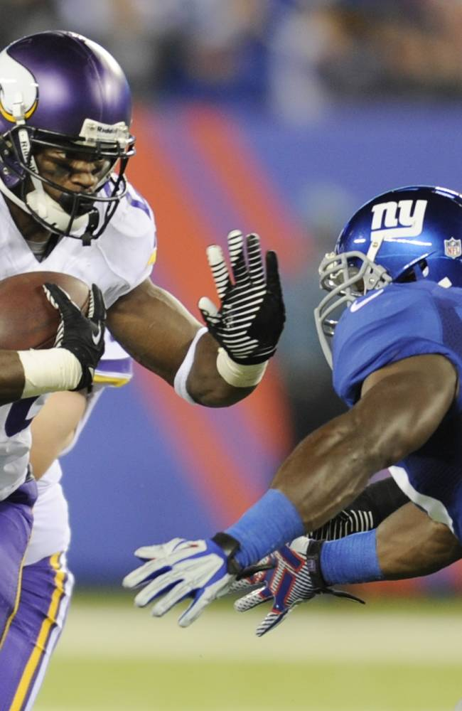 Minnesota Vikings running back Adrian Peterson (28) stiff-arms New York Giants' Jon Beason (52) during the second half of an NFL football game Monday, Oct. 21, 2013 in East Rutherford, N.J