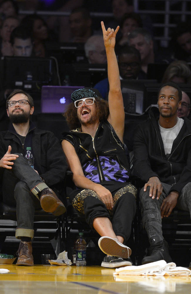 Singer, dancer and DJ Redfoo reacts as one of his songs is played during the second half of an NBA basketball game between the Los Angeles Lakers and the Sacramento Kings, Sunday, Nov. 24, 2013, in Los Angeles