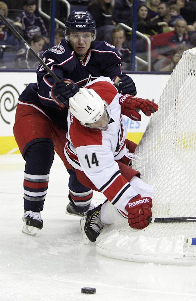 Columbus Blue Jackets' Ryan Murray, left, checks Carolina Hurricanes' Nathan Gerbe during the first period of an NHL hockey game on Thursday, Sept. 26, 2013, in Columbus, Ohio