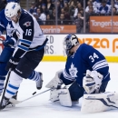 Toronto Maple Leafs goalie James Reimer (34) makes a save as he is screened by Winnipeg Jets forward Andrew Ladd (16) during first-period NHL hockey game action in Toronto, Saturday, April 5, 2014 The Associated Press