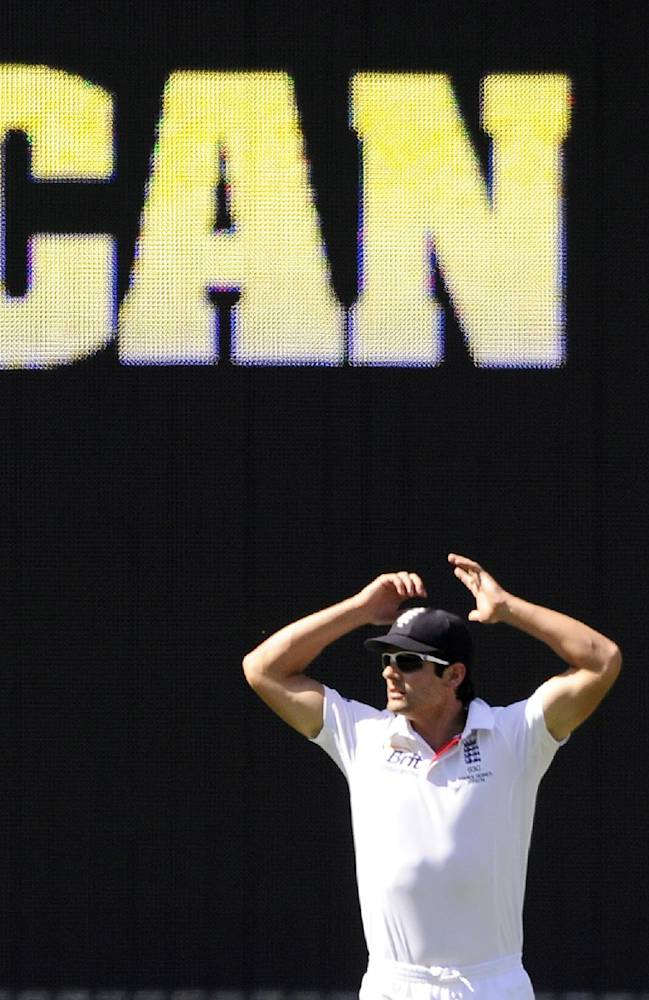 England's captain Alastair Cook raises his arms while fielding against Australia during their Ashes cricket test match, Friday, Dec. 27, 2013, at the Melbourne Cricket Ground in Melbourne, Australia. England made 255 runs in their first innings