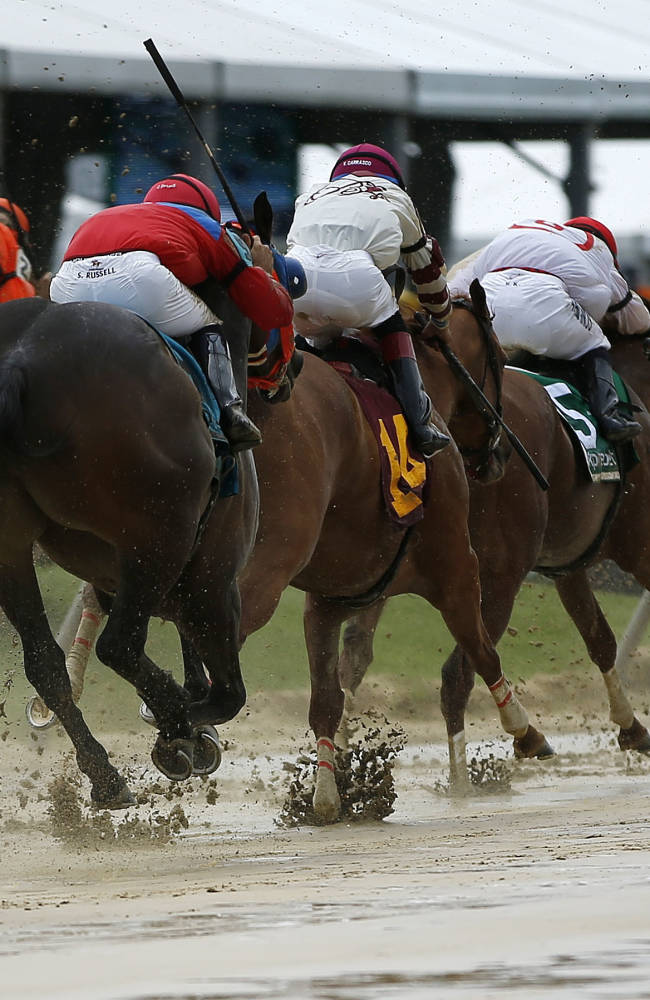 Horses race down a sloppy track during the second race before the Black-Eyed Susan Stakes horse race at Pimlico Race Course, Friday, May 16, 2014, in Baltimore. The 139th Preakness horse race takes place Saturday