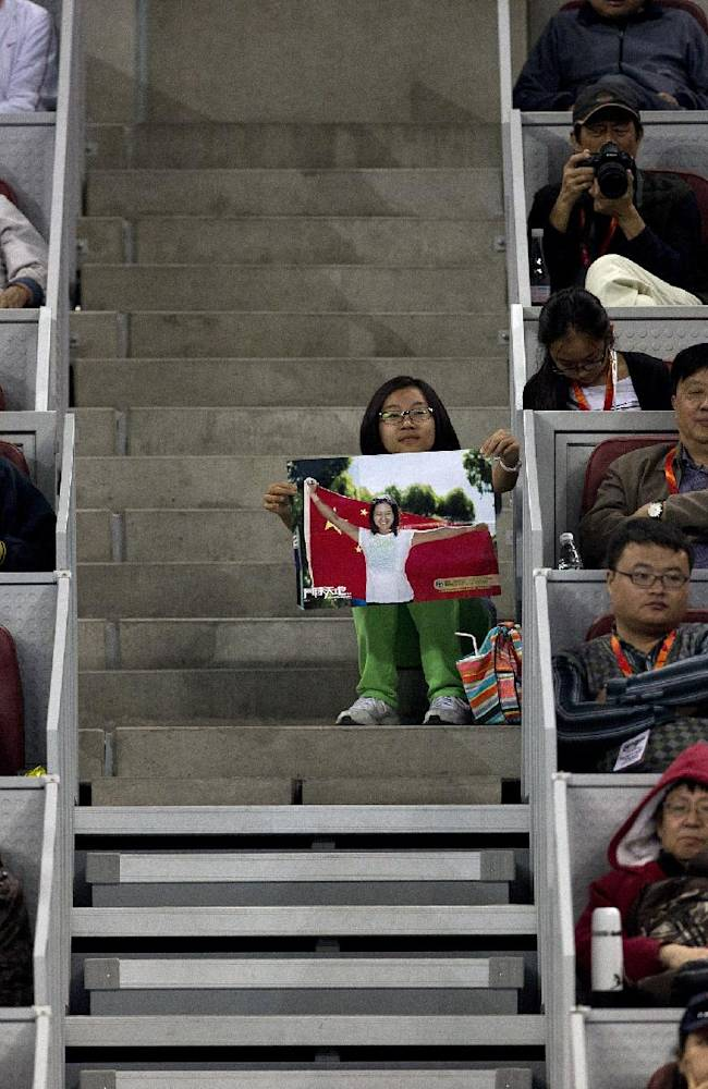 A woman, center, holding a picture of Li Na of China sits on the aisle of the stand as she watches Li's match against Sabine Lisicki of Germany in the China Open tennis tournament at the National Tennis Stadium in Beijing, China Wednesday, Oct. 2, 2013