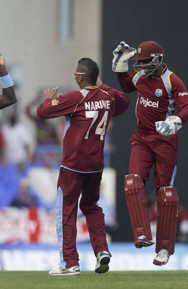CORRECTS TO SAY THAT THE WICKET WAS TAKEN FROM ENGLAND'S LUKE WRIGHT INSTEAD OF MICHAEL LUMB - From left, West Indies' Darren Sammy, Sunil Narine, Denesh Ramdin and captain Dwayne Bravo celebrate taking the wicket of  England's Luke Wright during their second one-day international cricket match at the Sir Vivian Richards Cricket Ground in St. John's, Antigua, Sunday, March 2, 2014