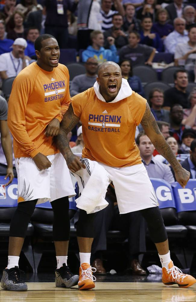 Phoenix Suns' P.J. Tucker, right, and Dionte Christmas cheers on their team from the bench during the first half of an NBA basketball game against the Indiana Pacers Wednesday, Jan. 22, 2014, in Phoenix