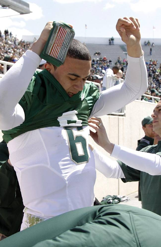 Michigan State quarterback Damion Terry switches from a white jersey to a green jersey during an NCAA college spring football scrimmage on Saturday, April 26, 2014, in East Lansing, Mich. Terry played for both the White team and the Green team. The White team won 20-13