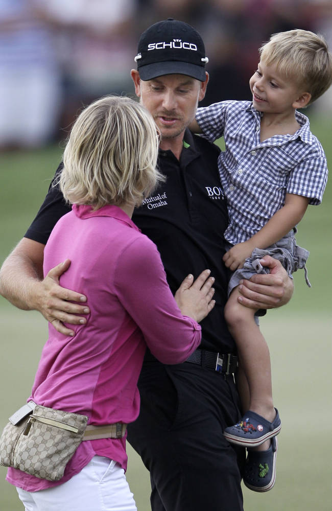 Henrik Stenson from Sweden celebrates with his son, Karl and wife Emma Lofgren after he won the final round of DP World Golf Championship in Dubai, United Arab Emirates, Sunday Nov. 17, 2013