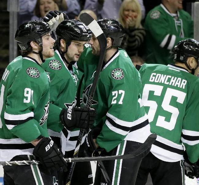 Dallas Stars' Tyler Seguin (91), Aaron Rome (27) and Sergei Gonchar (55) congratulate Jamie Benn (14) on his goal in the first period of an NHL hockey game against the Toronto Maple Leafs, Thursday, Jan. 23, 2014, in Dallas