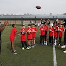 Oakland Raiders Usama Young, right, and Kevin Boothe, left, train children during an event at Guildford, England, Tuesday, Sept. 23, 2014. The Raiders will play the Miami Dolphins in an NFL football game at London's Wembley Stadium on Sunday Sept. 28. Th