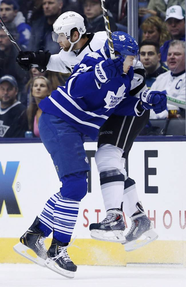 Toronto Maple Leafs' James van Riemsdyk collides with Los Angeles Kings' Jake Muzzin, back, during first period NHL hockey action in Toronto, Wednesdayn Dec. 11, 2013