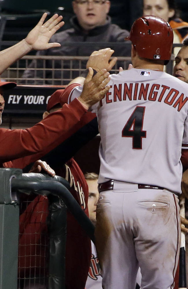 Arizona Diamondbacks' Cliff Pennington (4) is greeted in the dugout after scoring on a single from Tony Campana during the 10th inning of a baseball game on Thursday, April 10, 2014, in San Francisco. Arizona won 6-5