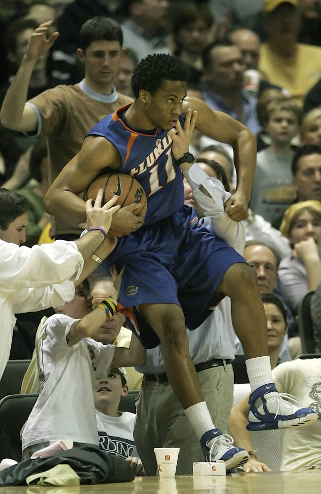In this Feb. 15, 2006, file photo, Florida guard Taurean Green gets some help from the fans to keep from falling into the crowd while playing Vanderbilt in the second half of a college basketball game in Nashville, Tenn. Oklahoma State All-American guard Marcus Smart is serving a three-game suspension for shoving a fan who later apologized for his actions. The incident shows how volatile the interaction between fans and athletes is becoming
