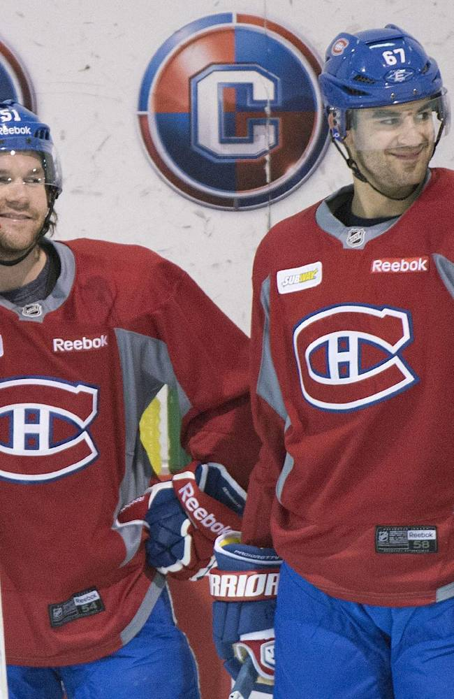 Montreal Canadiens' David Desharnais, left, and Max Pacioretty chat during a practice session in Brossard, Quebec,  Monday, April 21, 2014. The Canadiens lead Tampa Bay 3-0 in their best-of-seven series in the first round of the playoffs