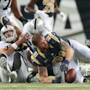 St. Louis Rams defensive end Chris Long (91) recovers a fumble forced by defensive end Robert Quinn, far left, on a sack of Oakland Raiders quarterback Matt Schaub, second from left, in fourth quarter action during a game between the St. Louis Rams and Oa