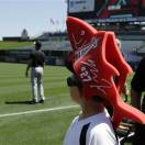 A boy wearing a Mike Trout headpiece watches a member of the White Sox on  the field with other kids, coaches and parents walking the warning track on LIttle League day at Angel Stadium before a baseball game between the Chicago White Sox and Los Angeles Angels in Anaheim, Calif., Sunday, May 19, 2013. (AP Photo/Reed Saxon)