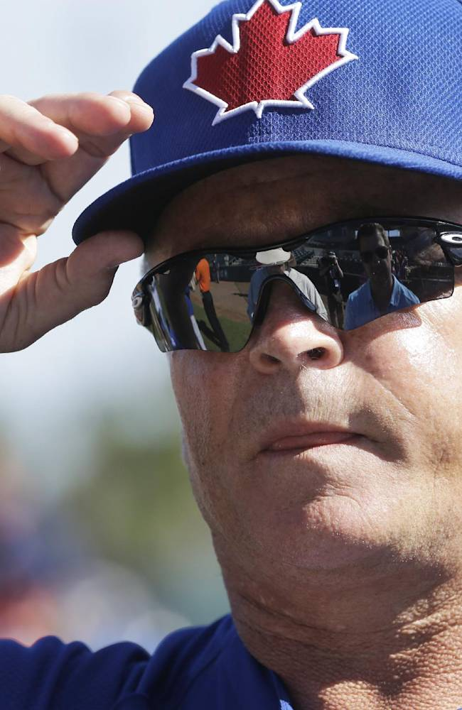 Toronto Blue Jays manager John Gibbons adjusts his cap before a spring training baseball game against the Houston Astros in Kissimmee, Fla., Sunday, March 9, 2014