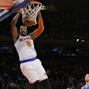 New York Knicks' J.R. Smith (8) dunks the ball during the first half of an NBA basketball game as Philadelphia 76ers' Michael Carter-Williams (1) trails the play Monday, March 10, 2014, in New York The Associated Press