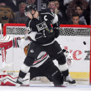Chicago Blackhawks goalie Corey Crawford, left, is scored on by Los Angeles Kings defenseman Jake Muzzin, not seen, as right wing Dustin Brown screens him during the third period of an NHL hockey game, Wednesday, Jan. 28, 2015, in Los Angeles. The Kings