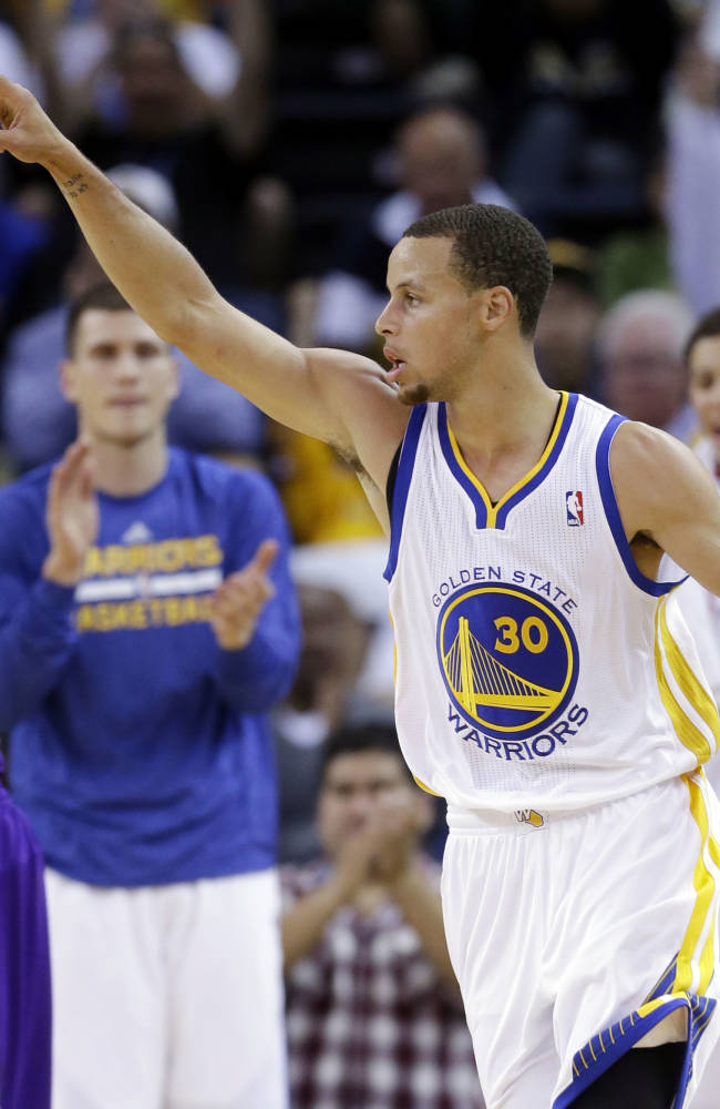 Golden State Warriors' Stephen Curry (30) celebrates after making a 2-point basket, next to Sacramento Kings' Isaiah Thomas (22) during the first half of an NBA preseason basketball game on Monday, Oct. 7, 2013, in Oakland, Calif