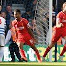 Liverpool's Raheem Sterling and Jordan Henderson, right, celebrate after Queens Park Rangers' Steven Caulker scored an own goal during their English Premier League soccer match at Loftus Road, London, Sunday, Oct. 19, 2014