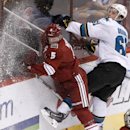 San Jose Sharks' Justin Braun (61) checks Phoenix Coyotes' Connor Murphy (5) into the boards during the third period of an NHL hockey game on Saturday, April 12, 2014, in Glendale, Ariz. The Sharks defeated the Coyotes 3-2 The Associated Press