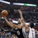 San Antonio Spurs' Tony Parker (9), of France, goes to the basket in front of Memphis Grizzlies' Mike Conley (11) in the second half of an NBA basketball game in Memphis, Tenn., Friday, Nov. 22, 2013. Parker scored 20 points in the Spurs' 102-86 victory o