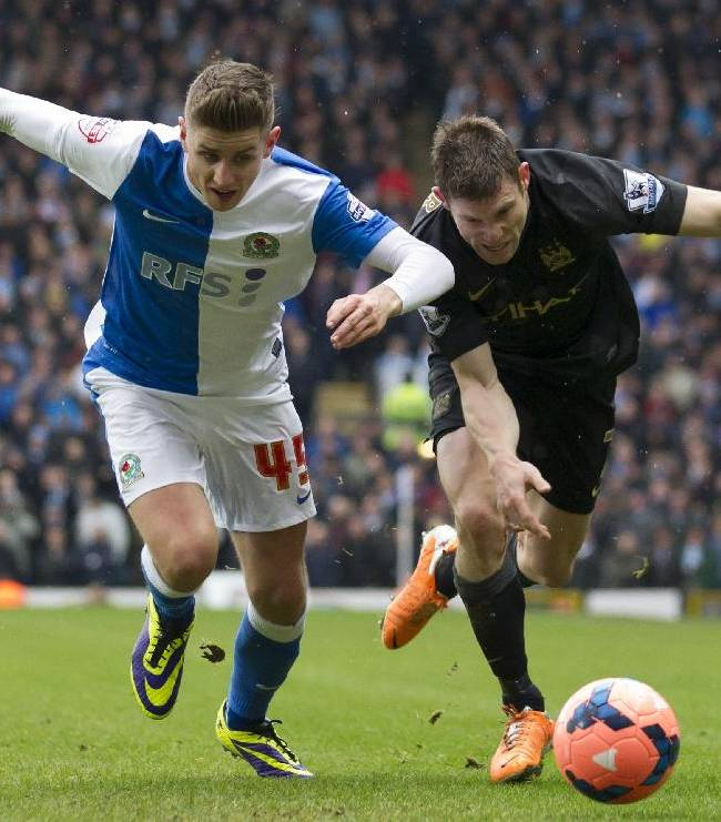 Manchester City's James Milner, right, fights for the ball against Blackburn Rovers' Tom Cairney during their English FA Cup third round soccer match at Ewood Park Stadium, Blackburn, England, Saturday, Jan. 4, 2014