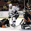 Los Angeles Kings center Trevor Lewis, middle, shoots between Anaheim Ducks defenseman Hampus Lindholm, left, and Anaheim Ducks goalie Jonas Hiller during the first period of an NHL hockey game in Anaheim, Calif., Tuesday, Dec. 3, 2013. (AP Photo/Chris Carlson)