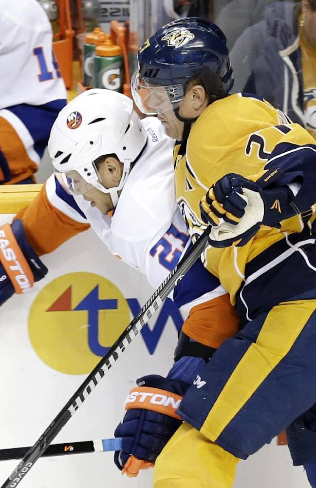 New York Islanders right wing Kyle Okposo (21) and Nashville Predators forward Patric Hornqvist (27), of Sweden, battle for the puck in the first period of an NHL hockey game on Saturday, Oct. 12, 2013, in Nashville, Tenn