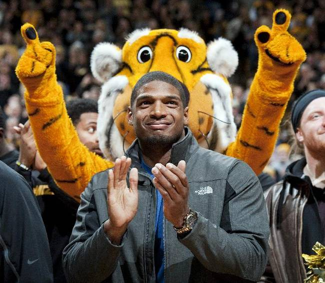In this Feb. 15, 2014, file photo, Missouri's All-American defensive end Michael Sam claps during the Cotton Bowl trophy presentation at halftime of an NCAA college basketball game between Missouri and Tennessee in Columbia, Mo.  Sam has been selected the winner of the Arthur Ashe Courage Award. The Missouri defensive end who likely will be drafted by an NFL team this weekend, will receive the award given to individuals who transcend sports at The 2014 ESPYs on July 16