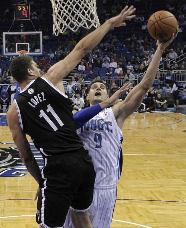 Orlando Magic's Nikola Vucevic (9), of Montenegro, takes a shot as he is guarded by Brooklyn Nets' Brook Lopez (11) during the first half of an NBA basketball game in Orlando, Fla., Sunday, Nov. 3, 2013