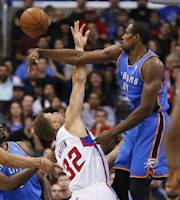 Oklahoma City Thunder forward Serge Ibaka, right, blocks a shot by Los Angeles Clippers forward Blake Griffin during the first half of an NBA basketball game in Los Angeles, Wednesday, April 9, 2014. (AP Photo/Danny Moloshok)