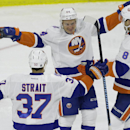 New York Islanders' Mikhail Grabovski (84), of Germany, celebrates his goal against the Carolina Hurricanes with Brian Strait (37) and Griffin Reinhart (8) during the third period of an NHL hockey game in Raleigh, N.C., Friday, Oct. 10, 2014. New York won